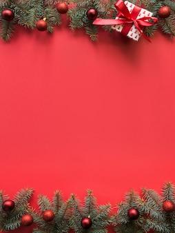 Cadre de noël avec des branches de sapin, des boules rouges sur fond rouge. copyspace, vue de dessus, mise à plat.