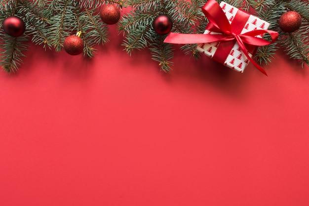 Cadre de noël avec des branches de sapin, des boules rouges, une guirlande sur fond rouge. copyspace, vue de dessus, mise à plat.