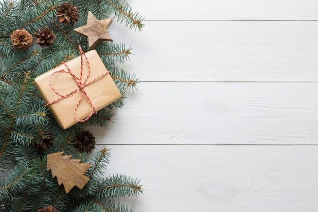Cadre de noël de branches de sapin, cadeau et jouets en bois sur une planche en bois blanche
