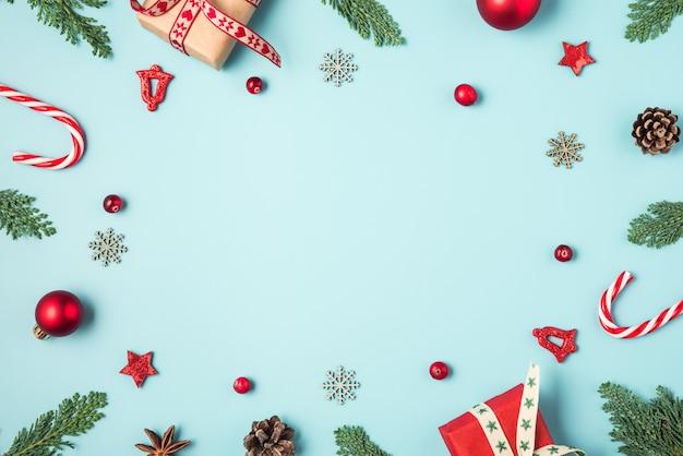Cadre de noël en branches de sapin, coffrets cadeaux, bonbons, décorations de vacances rouges et pommes de pin sur fond bleu