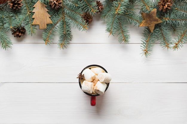 Cadre de noël de branches de sapin, jouets en bois et tasse de café avec guimauve au centre sur planche de bois blanc