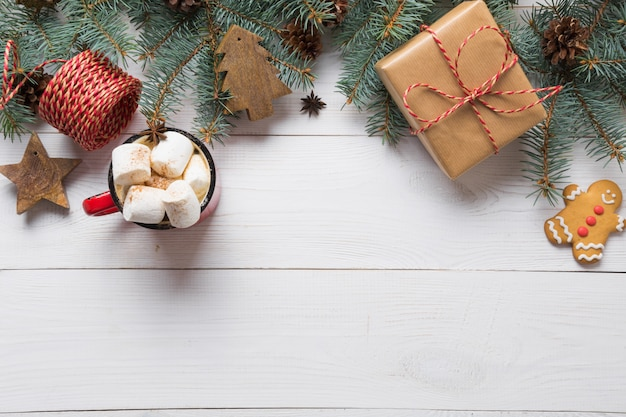Cadre de noël de branches de sapin, jouets en bois et tasse de café avec guimauve sur planche de bois blanc