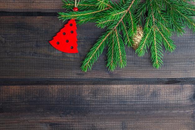 Cadre de noël des branches de sapin et ornement rouge suspendu sur fond de bois rustique