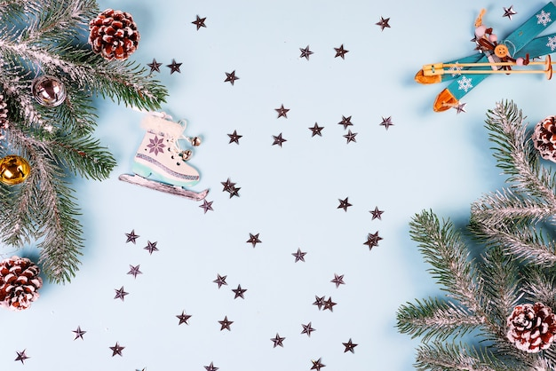 Cadre de noël-carte postale de jouets de noël décoratifs, sapin, cônes, boules, étoiles d'or, décorations en traîneau sur bleu