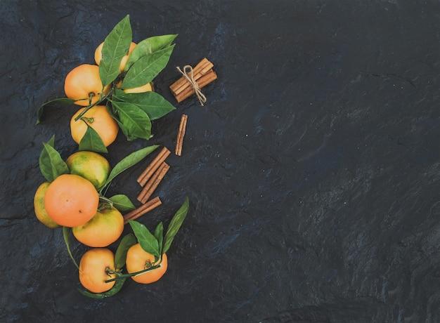 Cadre de noël ou du nouvel an. mandarines fraîches avec des feuilles, des bâtons de cannelle sur fond de pierre sombre, vue de dessus
