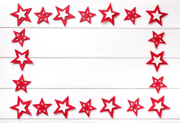 Cadre de noël avec des étoiles rouges sur fond en bois blanc.