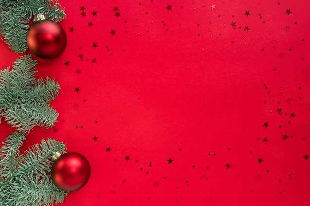 Cadre de noël fait de branches d'arbres, de paillettes et de boules sur une surface rouge. joyeux noël et bonne année concept