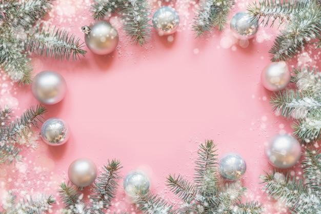 Cadre de noël fait de branches de sapin, décorations blanches enneigées, boules blanches sur table rose