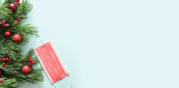 Cadre de noël de masque médical protecteur rouge et branches à feuilles persistantes sur fond bleu. bannière de vacances avec espace copie.