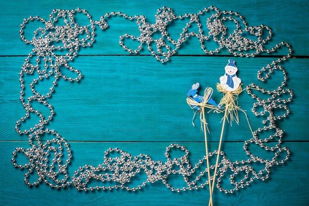 Cadre de noël avec des perles d'argent sur un fond en bois bleu