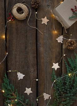 Cadre de noël vert de branches d'arbres frais, jouets de noël en bois et lumières