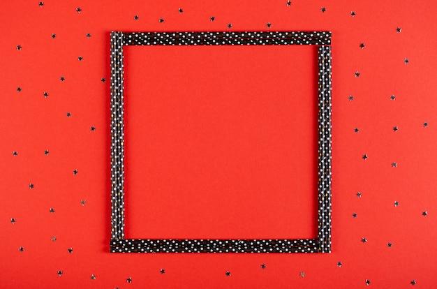 Cadre noir de composition de paille sur fond rouge, décoration de fête et de célébration.