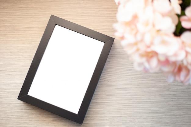 Cadre noir vide sur l'espace de travail de table bureau avec ordinateur portable et fleur
