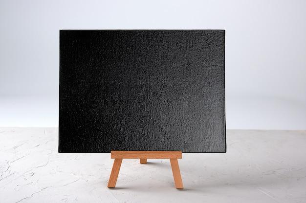 Cadre noir vide se dresse sur un trépied en bois