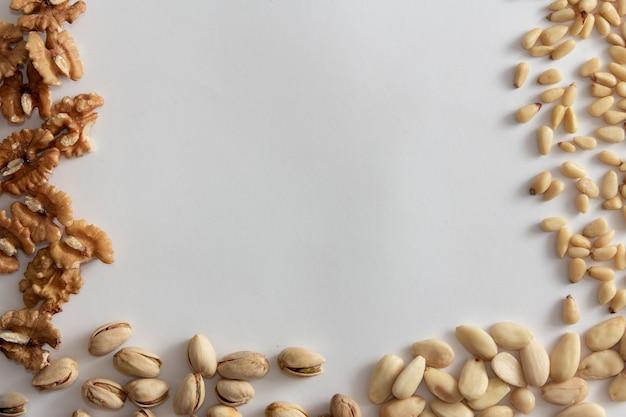 Cadre de noix avec des noix, des arachides, des amandes et des pignons sur fond blanc. espace de copie.