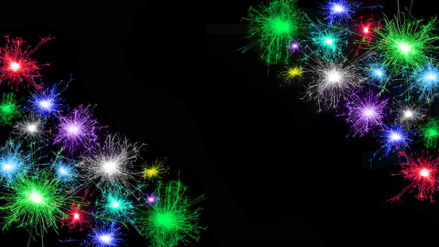 Cadre de nombreux feux d'artifice multicolores isolés sur fond noir. espace de copie. idée pour décorer les fêtes : noël, nouvel an, anniversaire, fête de l'indépendance, anniversaire