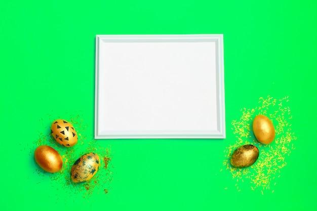 Cadre avec des oeufs de pâques tachetés d'or sur fond vert