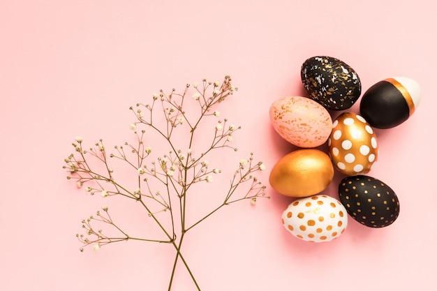Cadre en oeufs peints en bois aux couleurs or, noir et rose sur fond rose. joyeux fond de pâques avec espace copie