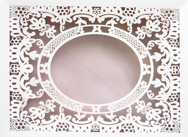 Cadre ovale en dentelle creuse en papier blanc, fait dans le style fleuri et luxueux sur fond rose