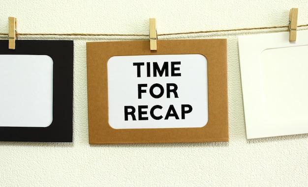 Cadre en papier kraft accroché au laçage sur fond de mur blanc avec espace. dans le cadre est écrit le texte time for recap.