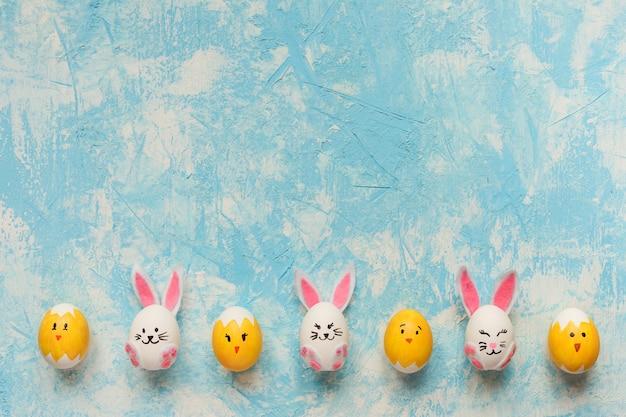Cadre de pâques décoré de lapins et de poussins sur la texture bleu ciel.