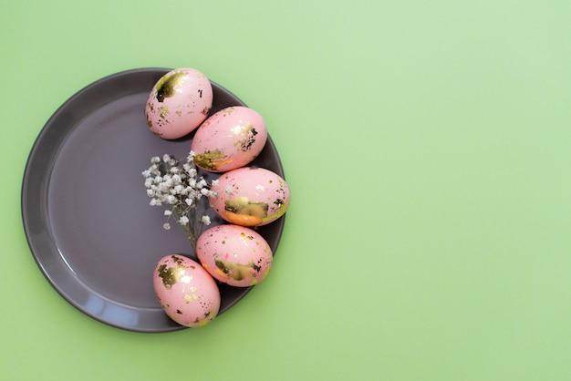 Cadre de pâques doré oeufs décorés sur fond vert pastel.
