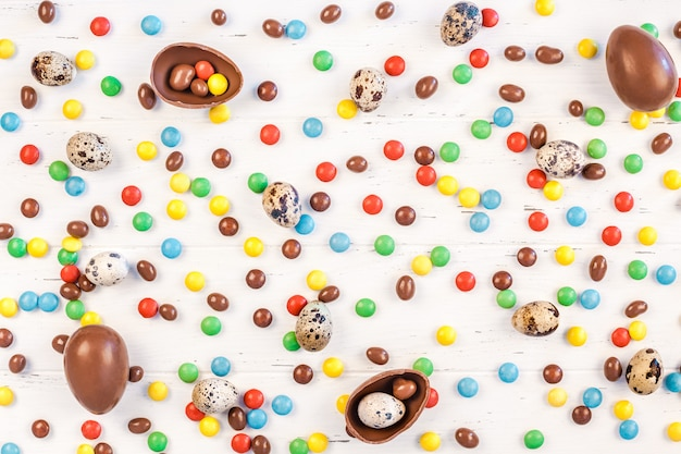 Cadre de pâques avec des œufs en chocolat, des bonbons colorés