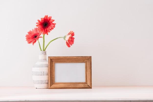 Cadre de paysage blanc simulé avec un vase de gerbera à côté du cadre, superposez votre citation, promotion, titre ou design, idéal pour les petites entreprises, les blogueurs lifestyle et les campagnes sur les réseaux sociaux