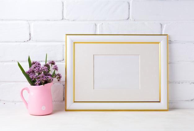 Cadre paysage décoré d'or avec des fleurs violettes dans un pichet rustique rose