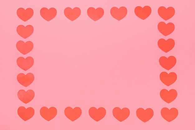 Cadre de petits coeurs rouges sur fond rose