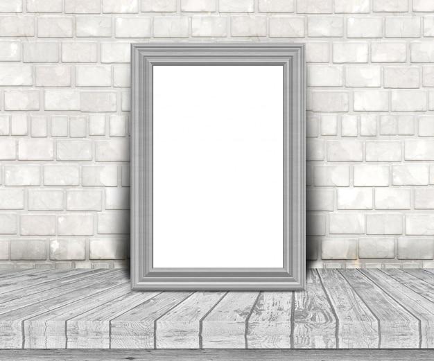 Cadre photo argent blanc 3d sur une table en bois, appuyé contre un mur de briques