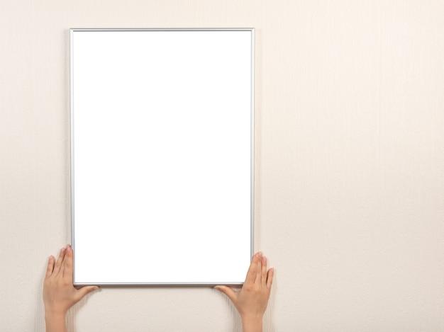 Cadre photo blanc argenté suspendu à un mur beige. mains tiennent le cadre photo sur le mur.