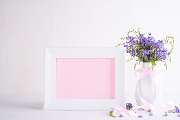 Cadre photo blanc avec belle fleur pourpre dans un vase sur une table en bois blanc.