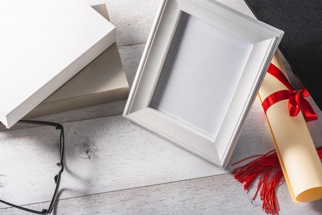 Cadre photo blanc blanc et matériel d'éducation ou de remise des diplômes sur une table blanche en bois