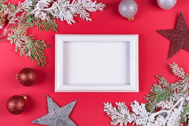Cadre photo blanc avec des branches et des ornements de noël