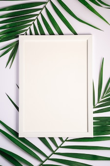 Cadre photo blanc avec modèle vide sur les feuilles de palmier, fond blanc, carte de maquette