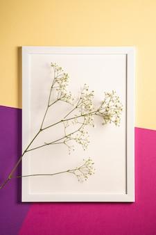 Cadre photo blanc avec modèle vide, fleurs de gypsophile, crème, violet et rose