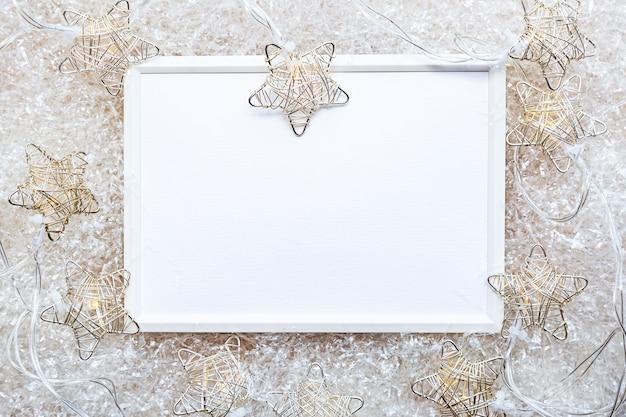 Cadre photo blanc sur un mur léger avec des guirlandes lumineuses