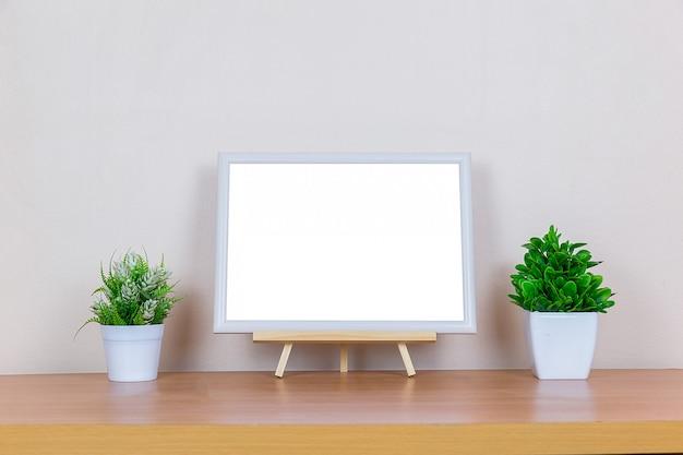 Cadre photo blanc sur table en bois.