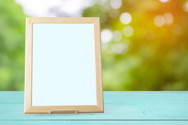 Cadre photo blanc vierge sur le mur et le bois de la table