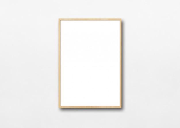 Cadre photo en bois accroché à un mur blanc