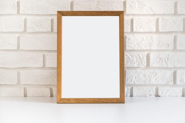 Cadre photo en bois blanc sur le mur de briques blanches avec espace copie