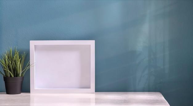 Cadre photo en bois blanc et plante d'intérieur sur table blanche