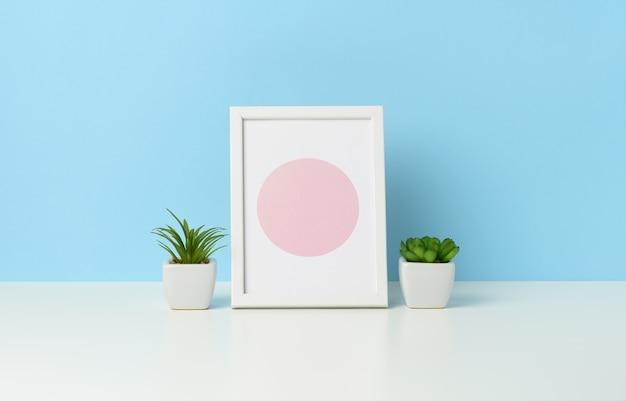 Cadre photo en bois blanc vide et pots de fleurs avec des plantes sur table blanche, fond bleu