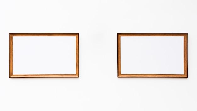 Cadre photo en bois brun sur le mur de ciment blanc - fond
