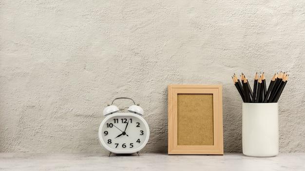Cadre photo en bois classique avec une horloge et des crayons dans une tasse à café blanche