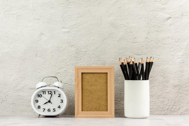 Cadre photo en bois classique avec une horloge et des crayons dans une tasse à café blanche.