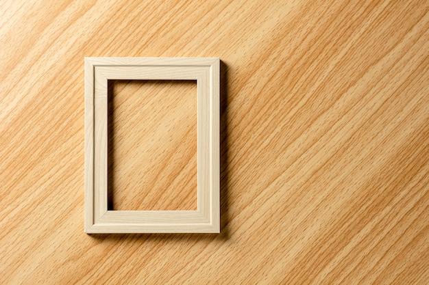 Cadre photo en bois classique vide sur le bureau en bois.