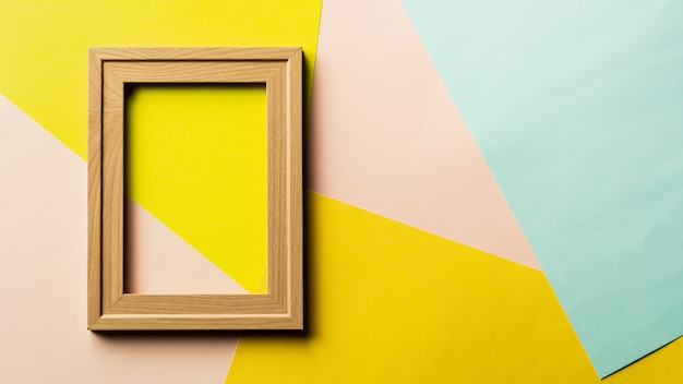 Cadre photo en bois classique vide sur fond rose, jaune et bleu.