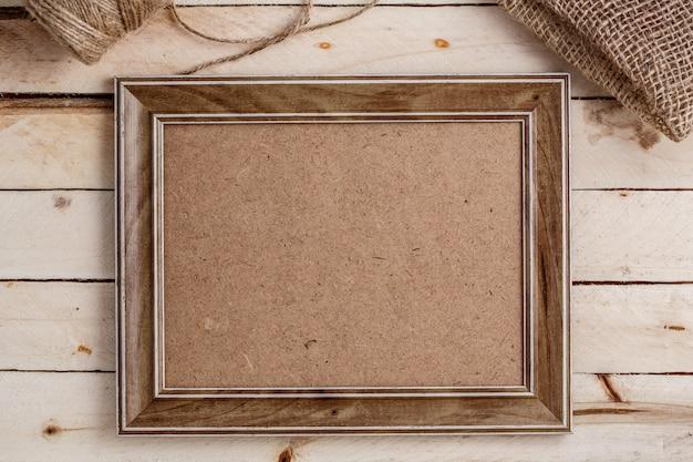 Cadre photo en bois sur fond en bois clair, vue de dessus, copysàce